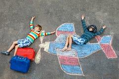 Två lilla barn, ungepojkar som har gyckel med med flygplanbildteckningen med färgrika chalks på asfalt vänner royaltyfria foton