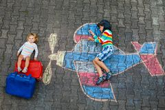Två lilla barn, ungepojke och litet barnflicka som har gyckel med med flygplanbildteckningen med färgrika chalks på fotografering för bildbyråer