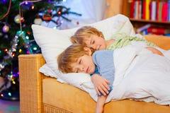 Två lilla blonda siblingpojkar som sover i säng på jul Royaltyfri Bild