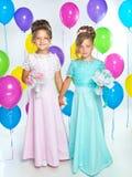 Två lilla brudtärnor med buketter i långa klänningar Arkivfoton