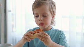 Två lilla caucasian pojkar som hemma äter pizza Dagljus lager videofilmer