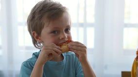 Två lilla caucasian pojkar som hemma äter pizza Dagljus arkivfilmer