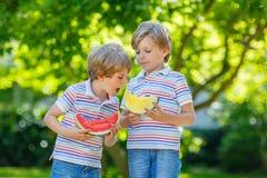 Två lilla förskole- ungepojkar som äter vattenmelon i sommar royaltyfria bilder