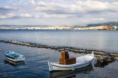 Två lilla fiskebåtar och staden av Thessaloniki, Grekland Royaltyfri Foto