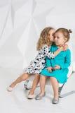 Två lilla flickvänner i de identiska klänningarna av olika färger som sitter på en stol i en studio med vita väggar Royaltyfri Fotografi