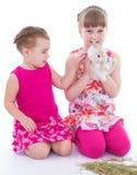 Två lilla flickvänner som slår kanin arkivfoto