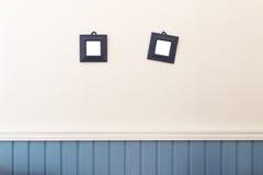 Två lilla fyrkantramar som hänger på vit- och blåttväggen Arkivfoton