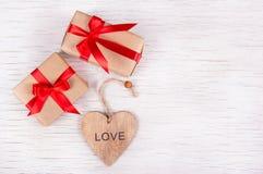 Två lilla gåvaaskar med röda band och handgjord valentin på en vit träbakgrund kopiera avstånd valentin för dag s Fotografering för Bildbyråer