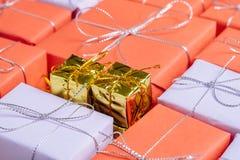 Två lilla guld- kulöra gåvor överst av gåvor arkivfoton