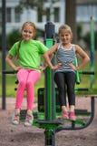 Två lilla gulliga flickor är förlovade i konditionutrustning royaltyfri foto