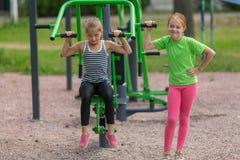 Två lilla gulliga flickor är förlovade i konditionutrustning arkivfoton