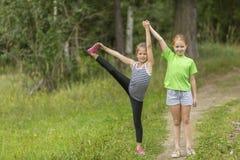 Två lilla gulliga flickor som utomhus värmer upp Fotografering för Bildbyråer