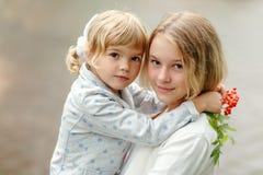 Två lilla härliga flickasystrar kram, närbildstående arkivfoton