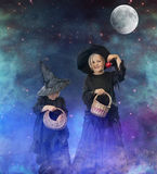 Två lilla halloween häxor på natten, med stjärnor och månen Royaltyfri Fotografi