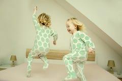 Två lilla identiska tvilling- systrar i identisk pyjamas och aktivt att ha gyckel på parent&en x27; s-säng, royaltyfria bilder