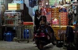 Två lilla kambodjanska flickor nära en motorsparkcykel Den lilla gatan shoppar lyckligt le f?r barn royaltyfri fotografi