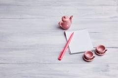 Två lilla koppar för rosa te med kokkärlet på en träbakgrund Kort med en anteckningsbok och en penna royaltyfria bilder
