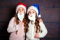 Två lilla le flickor som har gyckel Julfilial och klockor Le roliga systrar i jultomtenhatt på träbakgrund Fotografering för Bildbyråer