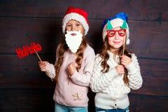 Två lilla le flickor som har gyckel Julfilial och klockor Le roliga systrar i jultomtenhatt på träbakgrund Royaltyfri Foto