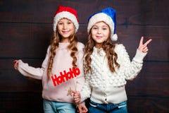 Två lilla le flickor som har gyckel Julfilial och klockor Le roliga systrar i jultomtenhatt på träbakgrund Royaltyfri Fotografi