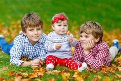 Två lilla lyckliga ungepojkar med nyfött behandla som ett barn flickan, gullig syster Fotografering för Bildbyråer