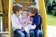 Två lilla lyckliga ungepojkar med nyfött behandla som ett barn flickan, gullig syster Royaltyfri Bild