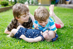 Två lilla lyckliga ungepojkar med nyfött behandla som ett barn flickan, gullig syster Arkivfoton