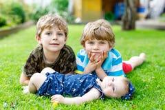 Två lilla lyckliga ungepojkar med nyfött behandla som ett barn flickan, gullig syster Arkivbilder