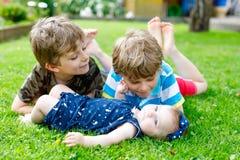 Två lilla lyckliga ungepojkar med nyfött behandla som ett barn flickan, gullig syster Royaltyfria Bilder