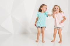 Två lilla roliga och skratta flicka i den identiska kläderna av olika färger som spelar i den vita studion Royaltyfri Bild