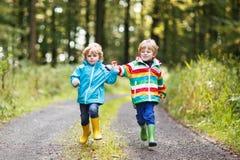 Två lilla siblingpojkar i färgrikt gå för regnrockar och för kängor Royaltyfri Foto