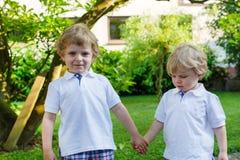 Två lilla siblingpojkar som har rolig det fria i familjblick arkivfoton