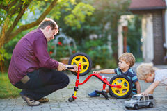 Två lilla siblingpojkar som reparerar cykelhjulet med fadern Royaltyfri Foto
