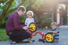 Två lilla siblingpojkar som reparerar cykelhjulet med fadern Royaltyfri Fotografi