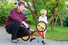 Två lilla siblingpojkar som reparerar cykelhjulet med fadern Arkivbilder
