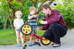 Två lilla siblingpojkar som reparerar cykelhjulet med fadern Arkivfoton