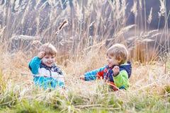 Två lilla siblingpojkar som slåss och har gyckel Fotografering för Bildbyråer