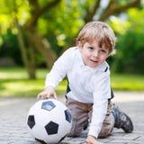Två lilla siblingpojkar som spelar fotboll och fotboll Royaltyfri Bild