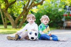 Två lilla siblingpojkar som spelar fotboll och fotboll Royaltyfri Foto