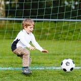 Två lilla siblingpojkar som spelar fotboll och fotboll på fält Royaltyfri Fotografi