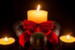 Två lilla stearinljus runt om en större stearinljus med juljordklot a Arkivfoton