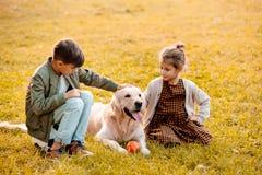 Två lilla syskon som daltar en hund och sitter på gräs royaltyfri foto