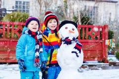 Två lilla syskonpojkar som in gör en snögubbe fotografering för bildbyråer