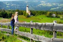 Två lilla systrar för adorables som beundrar härligt landskap i Dolomitesbergskedja, södra Tyrol, Italien royaltyfri foto