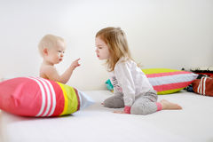 Två lilla systrar i säng på morgon Fotografering för Bildbyråer