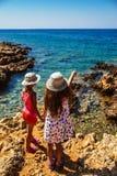 Två lilla systrar på steniga kuster av havet Arkivfoto
