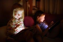 Två lilla systrar som använder den digitala minnestavladatoren Royaltyfri Bild