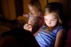 Två lilla systrar som använder den digitala minnestavladatoren Royaltyfria Foton