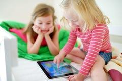 Två lilla systrar som använder den digitala minnestavladatoren Arkivbilder