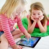 Två lilla systrar som använder den digitala minnestavladatoren Royaltyfria Bilder